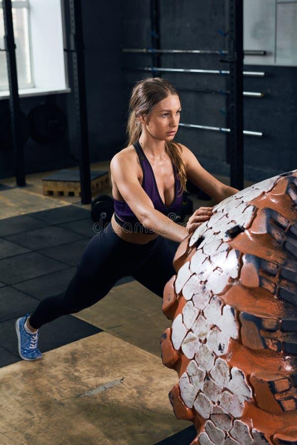 Junge Frau, die Reifen in der Turnhalle leicht schlägt lizenzfreies stockbild