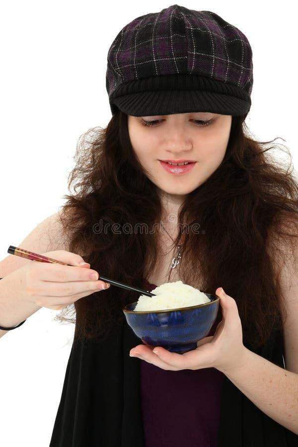 Junge Frau, die Reis mit Ess-Stäbchen isst lizenzfreie stockfotografie