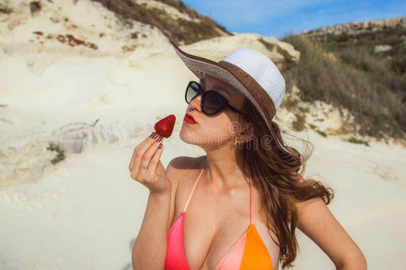 Junge Frau, die rote Erdbeere isst stockfotografie
