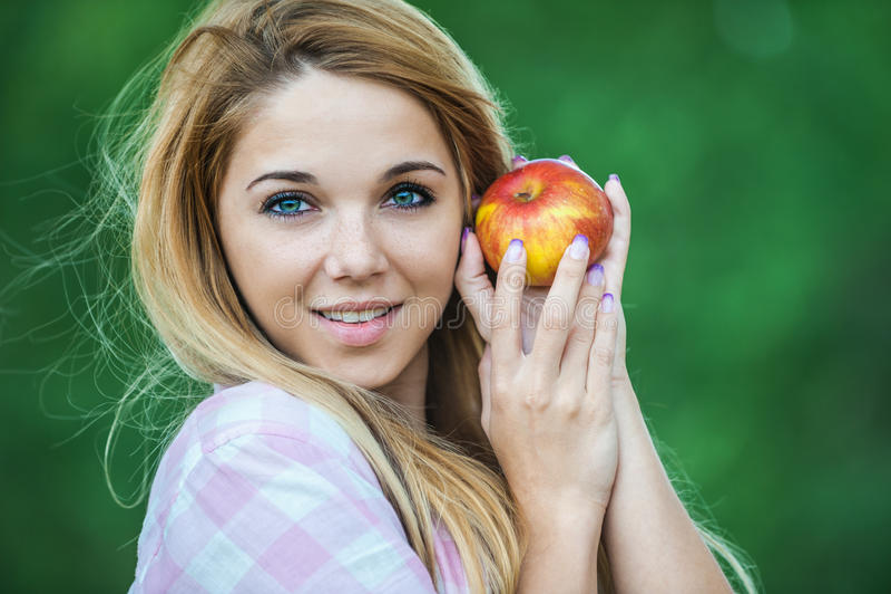 Junge Frau, die roten Apfel anbietet lizenzfreie stockfotografie