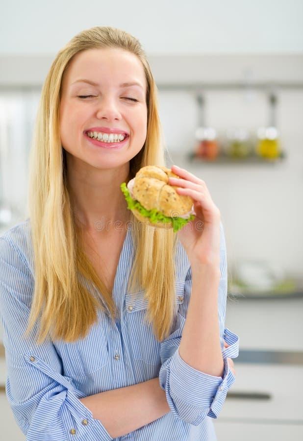 Junge Frau, die Sandwich isst lizenzfreie stockfotos