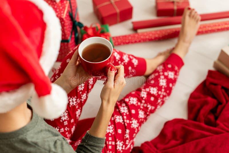 Junge Frau, die Sankt-Hut und Weihnachtspyjamas sitzen auf dem Boden unter eingewickelten Weihnachtsgeschenken, trinkender heißer lizenzfreie stockfotos