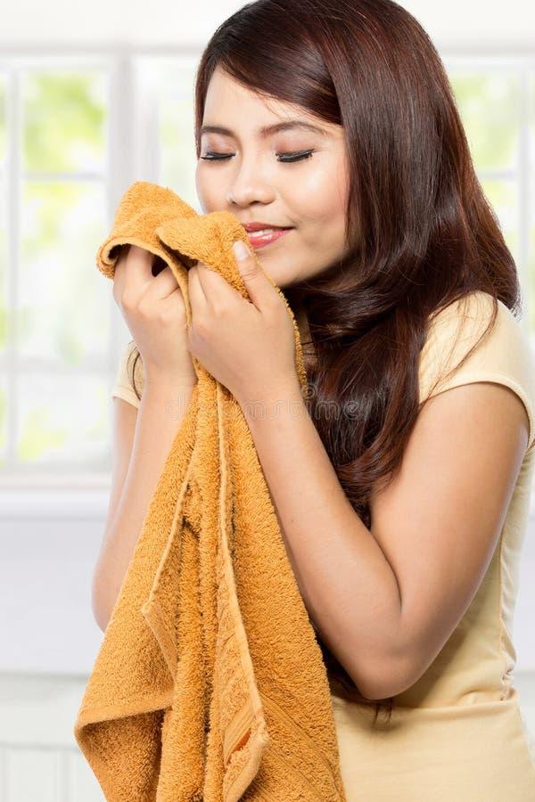Junge Frau, die saubere frische Wäscherei riecht stockbilder