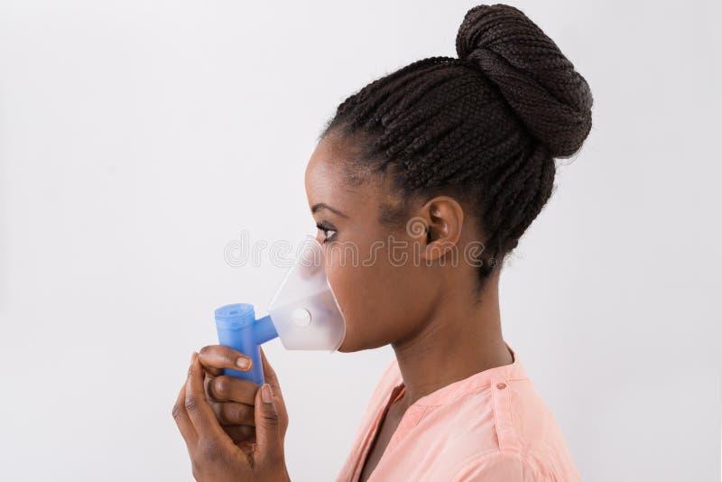 Junge Frau, die Sauerstoffmaske verwendet stockbild