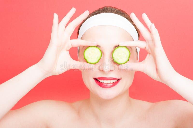 Junge Frau, die Scheiben der Gurke auf Augen hält stockfotos