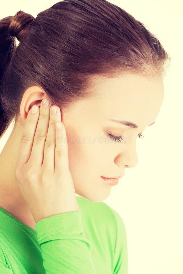 Junge Frau, die Schmerz im Ohr glaubt lizenzfreie stockfotografie