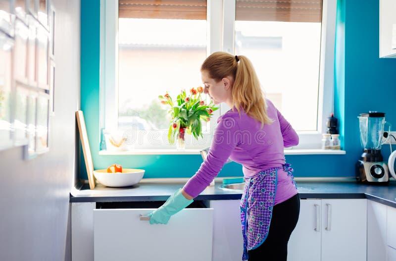 Junge Frau, die schmutzige Teller zur Spülmaschine setzt lizenzfreies stockbild