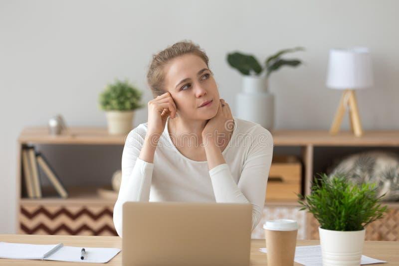 Junge Frau, die am Schreibtisch und am Denken sitzt lizenzfreie stockfotos