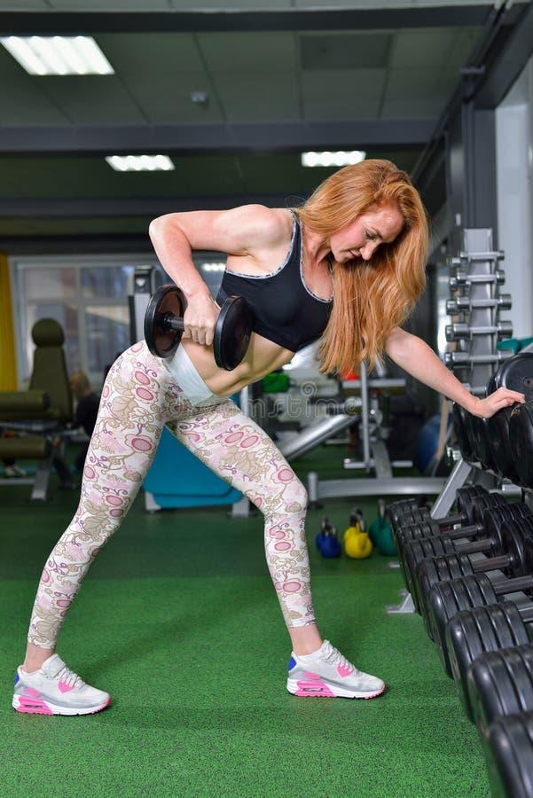 Junge Frau, die Schwergewichts- Übung für breitesten Muskel der Rückseite mit Dummköpfen an der Turnhalle tut lizenzfreie stockfotos