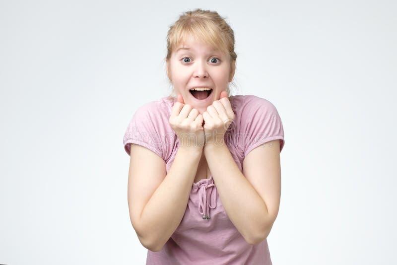Junge Frau, die sehr glückliches überraschtes Händchenhalten nahe dem Kopf überrascht wird lächelt stockbilder