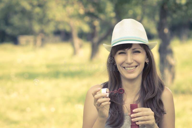 Junge Frau, die Seifenblasen im Sommerpark macht stockbild