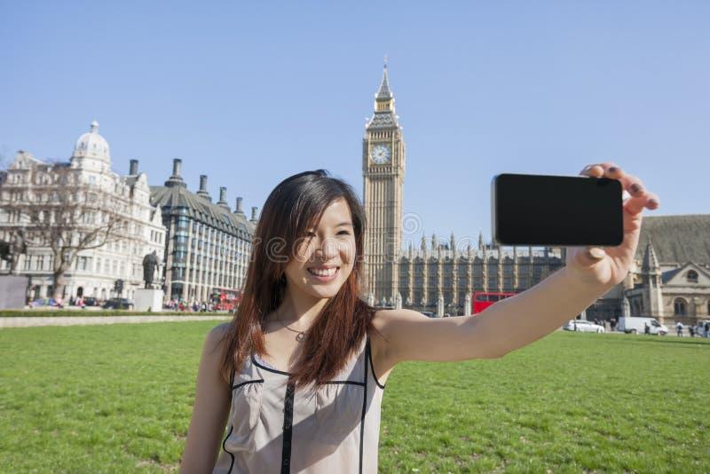 Junge Frau, die Selbstporträt durch intelligentes Telefon gegen Big Ben in London, England, Großbritannien nimmt stockbilder