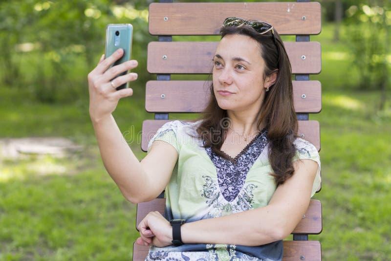 Junge Frau, die selfie im Park macht Sexy junge Frau mit dem langen blonden Haar, das selfie am Sommertag im Park tut Freundliche stockfotografie