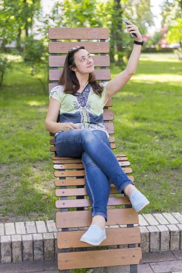 Junge Frau, die selfie im Park macht Sexy junge Frau mit dem langen blonden Haar, das selfie am Sommertag im Park tut Vertikales  lizenzfreies stockbild