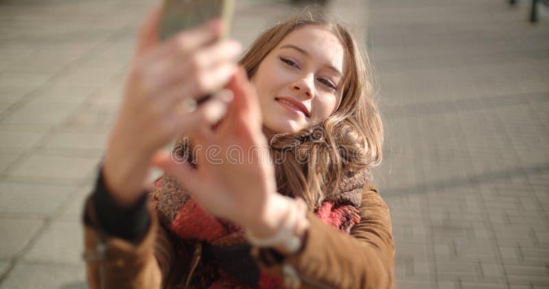 Junge Frau, die selfie mit Handy in der sonnigen Stadtstraße nimmt lizenzfreies stockbild
