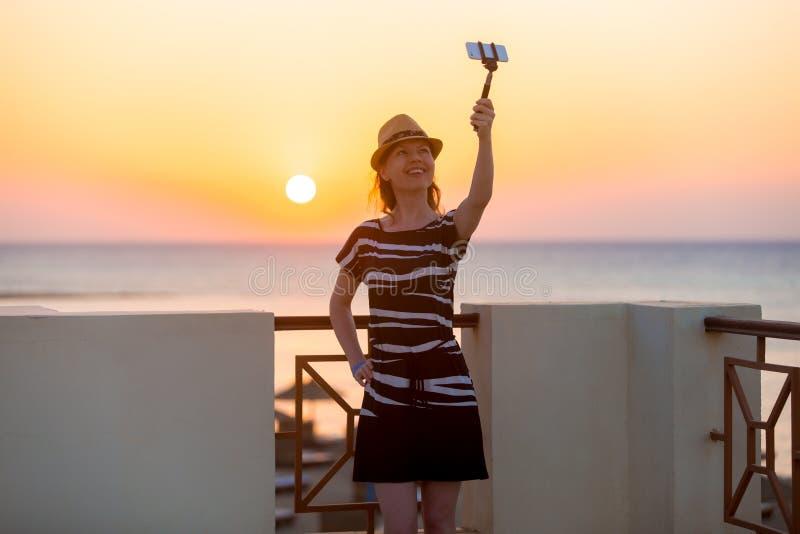 Junge Frau, die selfie mit Seesonnenuntergang nimmt stockfoto