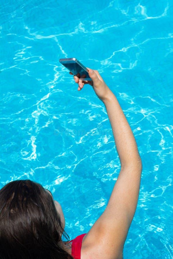 Junge Frau, die selfie am Swimmingpool nimmt lizenzfreies stockbild