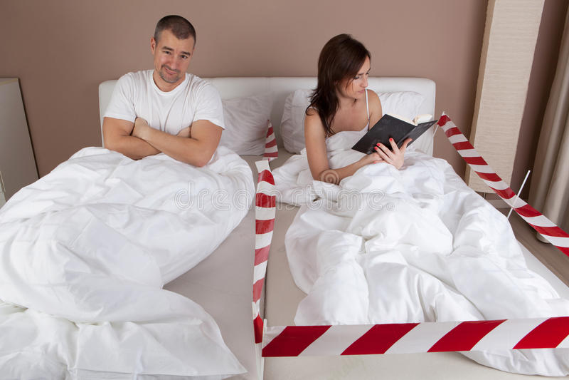Junge Frau, die separat vom Ehemann auf dem Bett und dem Ablesen liegt lizenzfreie stockfotos