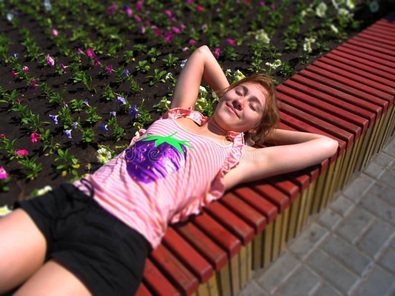 Junge Frau, die serenely auf der Bank in einem ein Sonnenbad nehmenden Park liegt stockfotografie