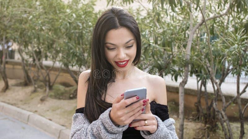Junge Frau, die Smartphone im Stadtpark schaut lizenzfreie stockfotos