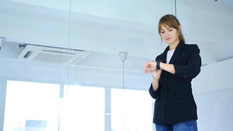 Junge Frau, die smartwatch bei der Arbeit im Büro verwendet stockbilder