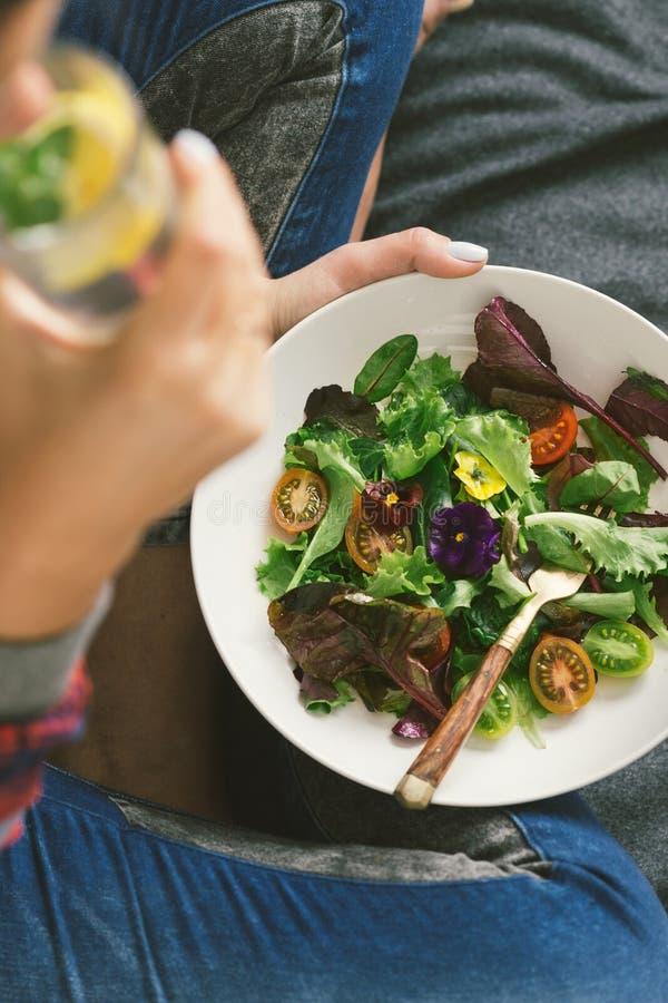 Junge Frau, die Sommersalatgemüse-Blumenbett gesundes f isst lizenzfreie stockbilder