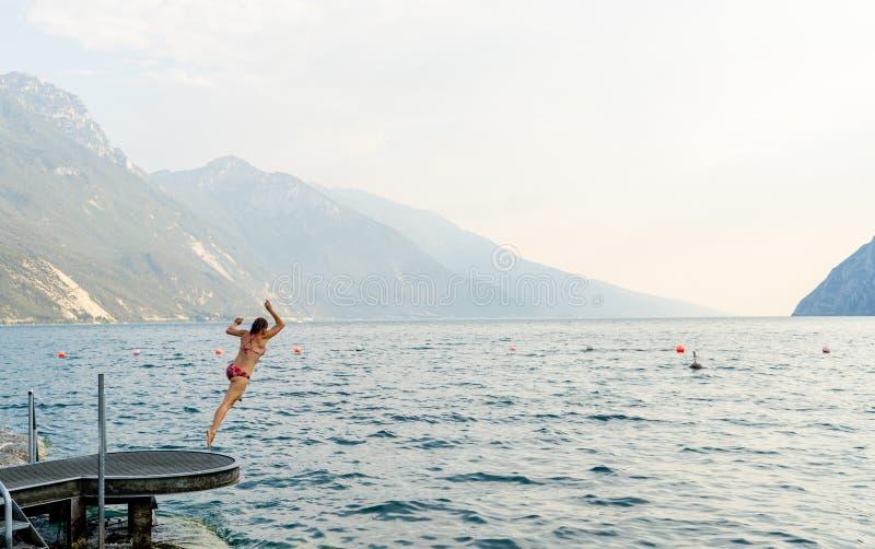 Junge Frau, die Spaß hat und in das Wasser in lake Lago di Garda in Italien während der Feiertage springt lizenzfreie stockbilder