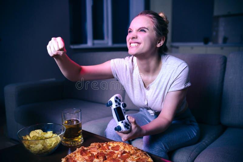 Junge Frau, die Spiel nachts spielt Verärgerte zujubelnde vorbildliche Griffhand in der Faust Gamepad Ungesunde Fertigkost auf Ta stockbild