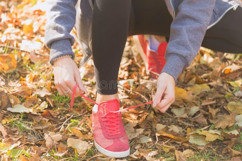 Junge Frau, die Spitzee von Laufschuhen vor dem Rütteln im Freien bindet stockfoto