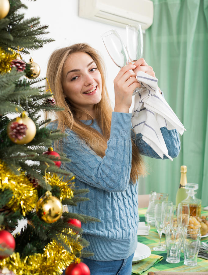 Junge Frau, die Stellen von den Gläsern vor Weihnachten entfernt lizenzfreie stockfotografie