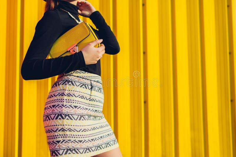 Junge Frau, die stilvolle gelbe Handtasche h?lt Fr?hlingsfrauenkleider und -zus?tze Art und Weise stockfotografie