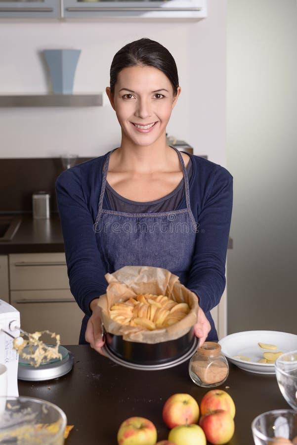 Junge Frau, die stolz ihren Apfelkuchen darstellt stockfotos