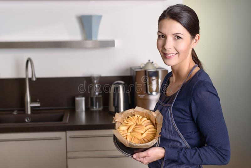 Junge Frau, die stolz ihren Apfelkuchen darstellt lizenzfreie stockfotografie