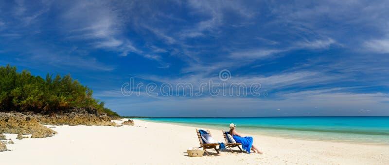Junge Frau, die am Strand sich entspannt stockbild