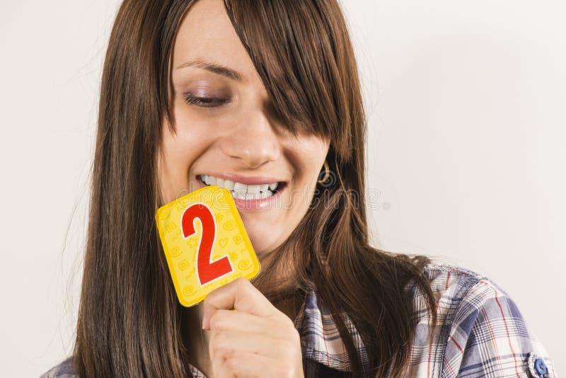 Junge Frau, die Tabelle zwei hält lizenzfreies stockfoto