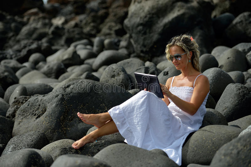 Junge Frau, die Tablette auf felsigem Strand verwendet stockbild