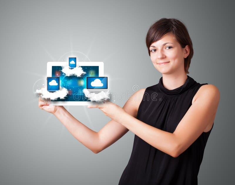 Junge Frau, die Tablette mit modernen Einheiten in den Wolken anhält lizenzfreie stockfotografie