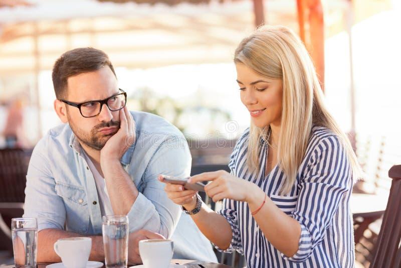 Junge Frau, die Telefon beim Sitzen am Café mit ihrem Freund verwendet lizenzfreies stockfoto