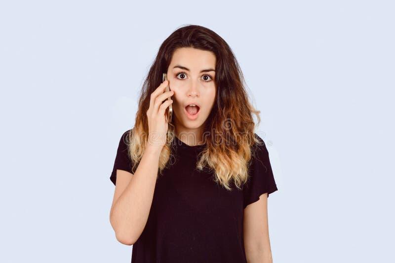 Junge Frau, die am Telefon mit ?berraschtem Blick spricht lizenzfreie stockbilder