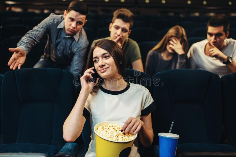 Junge Frau, die telefonisch im Kino spricht stockbilder
