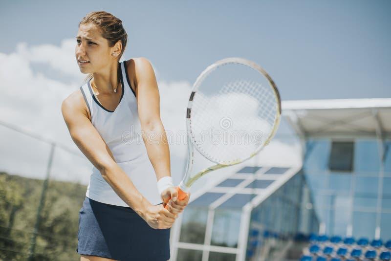 Junge Frau, die Tennis spielt stockfoto