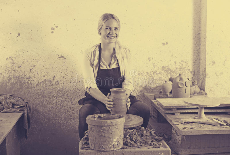 Junge Frau, die Topf unter Verwendung der Töpferscheibe herstellt stockfotografie