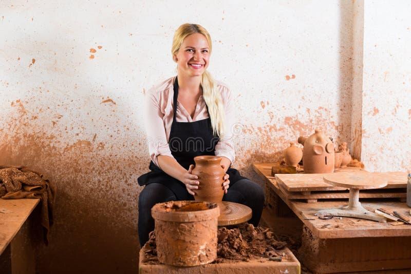 Junge Frau, die Topf unter Verwendung der Töpferscheibe herstellt stockbilder