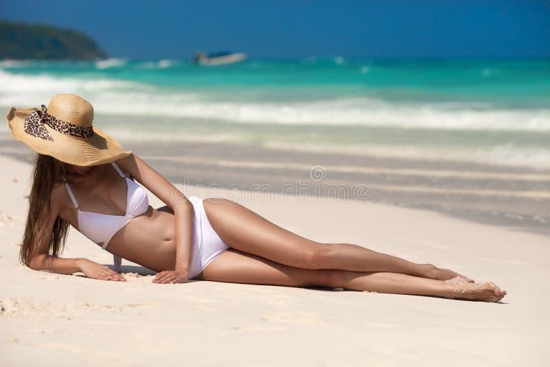 Junge Frau, die am tropischen Strand ein Sonnenbad nimmt stockfotografie