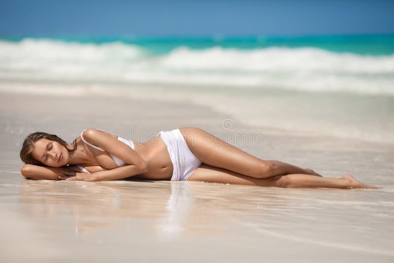Junge Frau, die am tropischen Strand ein Sonnenbad nimmt stockbild