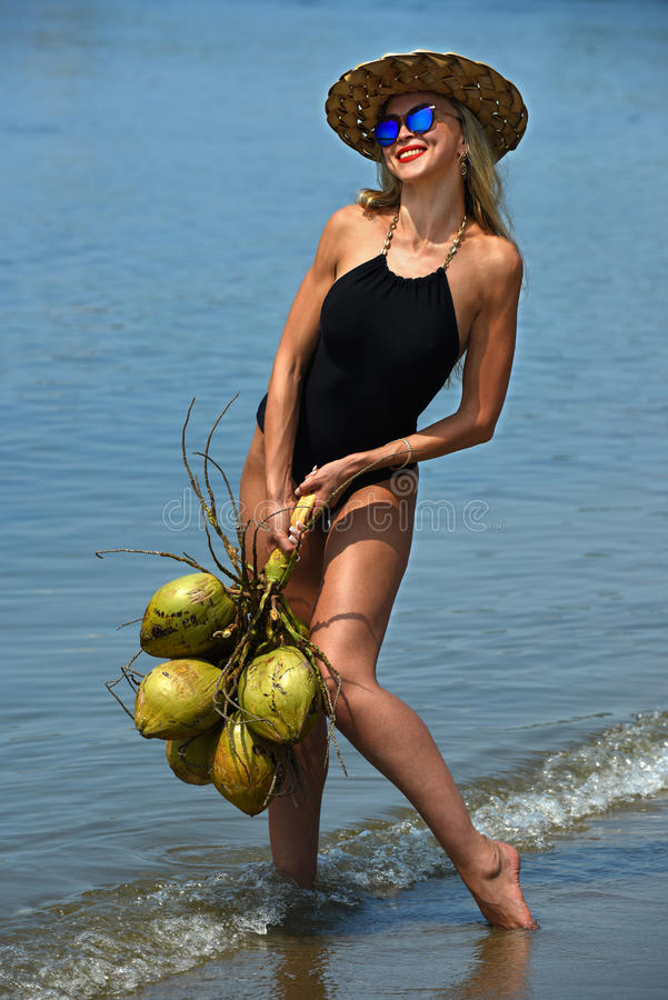 Junge Frau, die am tropischen Strand mit Kokosnüssen aufwirft stockbilder