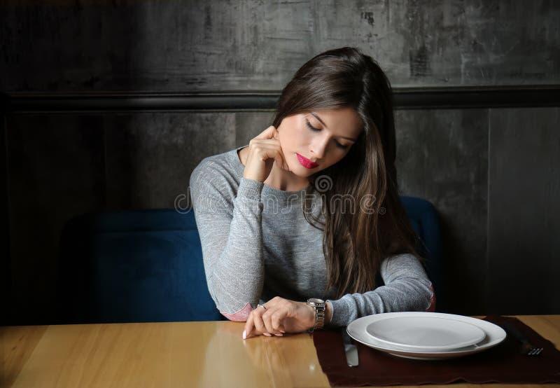 Junge Frau, die Uhr beim Warten auf ihren Freund im Restaurant betrachtet stockfotografie