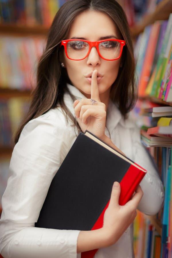 Junge Frau, die um Ruhe in der Bibliothek bittet stockfotografie