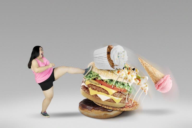 Junge Frau, die ungesunde Nahrungsmittel tritt lizenzfreie stockfotografie