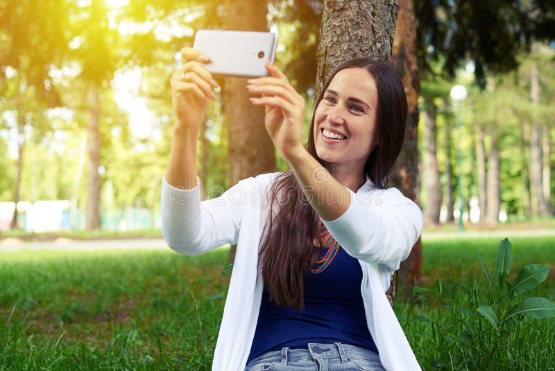Junge Frau, die unter dem Baum im Park sitzt und selfi macht lizenzfreie stockbilder
